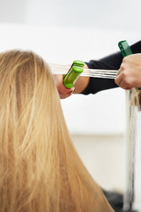 Hairdresser curling hair with straightener