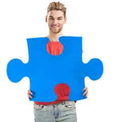 Young man holding a puzzle piece