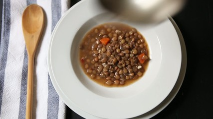 serving lentil soup on bowl