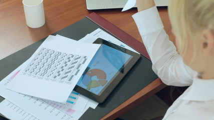 Business woman considers graphs and data on paper in office