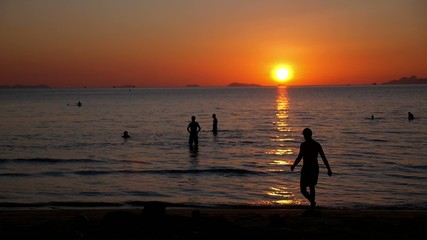 Silhouettes of People Swimming in the Sea at Amazing Sunset.
