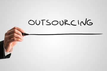 Man writing the word Outsourcing