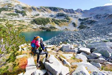 Woman backpacker standing mountain lake.