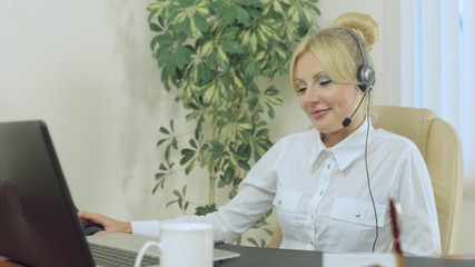 Nice blonde in the office with headphones speaks on microphone