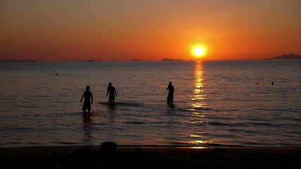 Silhouettes of Happy Young People Swimming in Sea against Sunset