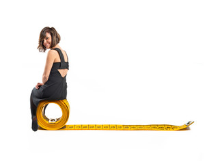 Woman sitting on tape measure over white background