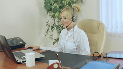 Attractive girl sitting in office with headphones and talking