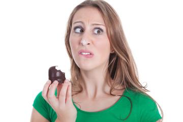 Junge Frau schielt auf Nase und blickt komisch mit Schokokuss