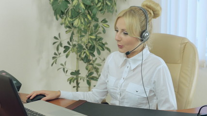 Blonde in headphones communicate with customers on the