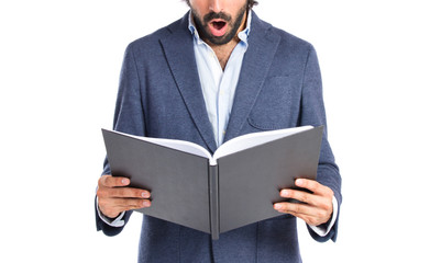 Surprised man reading a book over white background