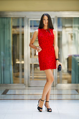 Beautiful woman in red dress in the shop