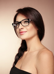Elegant charming woman wearing eyeglasses posing in studio