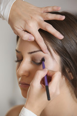 Beautiful woman doing make-up on face