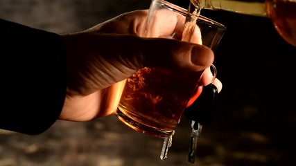 pouring alcohol into the glass,driver hold ignition key