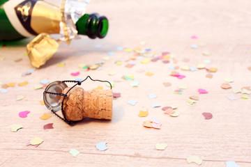 Sektflasche, Korken und Konfetti zum Jahreswechsel