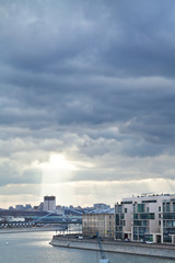 dark rainy clouds and sunbeams over Moscow city