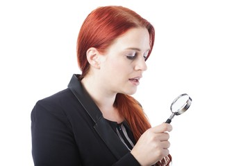 Attractive redhead holding a magnifying glass