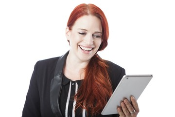 Redhead woman laughing as she reads her tablet