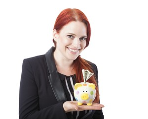 Pretty elegant redhead woman with a piggy bank