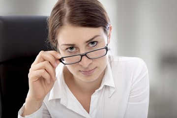 business woman sitting desk looking over glasses