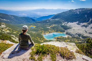 Woman sitting mountain edge above lake.