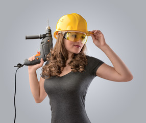 worker girl in a helmet with a drill