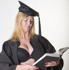 Mature female student in cap and gown reading a book
