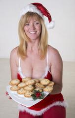 Woman in Santa fancy dress holding plate of Mince Pies