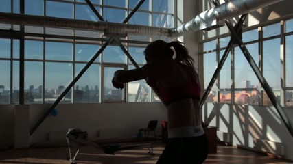 Woman boxing with big window as a background