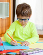 child with glasses drawing