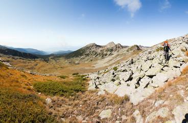 Backpacker woman walking rocky mountain slope.