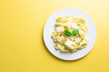 Italian tortellini pasta with basil and parmesan on yellow