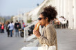 Attractive african american woman eating food outdoors - 73114518