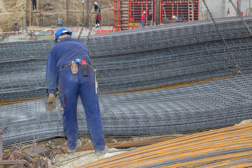 Iron worker unloading reinforcing steel from crane for construct