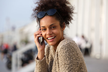 Happy african american woman calling by cellphone outdoors