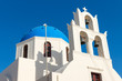 canvas print picture - White church with a blue roof seen in Oia