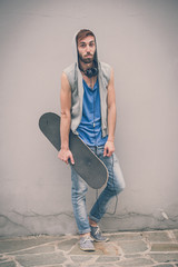 young hipster gay man with skate