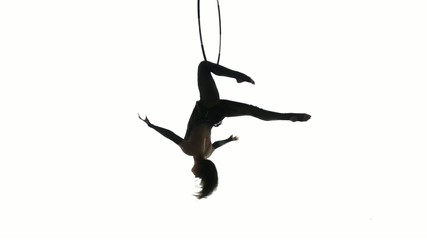 Aerial acrobat man on circus stage. Silhouette on a white