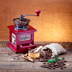 bag of coffee beans spilling and retro coffee grinder on table