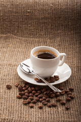 cup of coffee, grains on burlap tablecloth