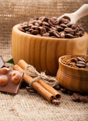 coffee beans in wooden bowl and chocolate on burlap tablecloth