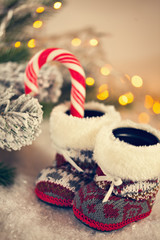 Baby Slippers Near With Candy Cane On Snowy Background