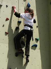 Lady climbing on practice wall