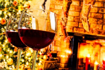 detail of two red wine glasses against christmas tree background