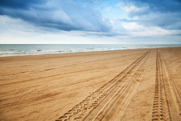 Perspective of tyre tracks on sandy beach