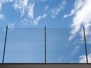 Metal Rabitz mesh fence against blue sky