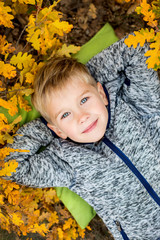 Toddler boy portrait lying in autumn