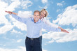 Couple With Arms Outstretched Standing Against Cloudy Sky