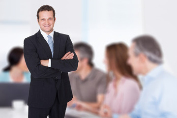 Businessman With Arms Crossed Standing In Boardroom