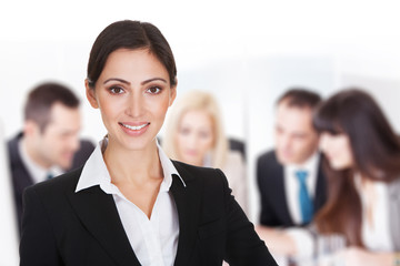 Smiling Businesswoman Against Team Discussing In Boardroom